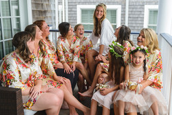 A bride and her bridesmaids on the porch of their hotel room in Edgartown photo by David Welch Photography