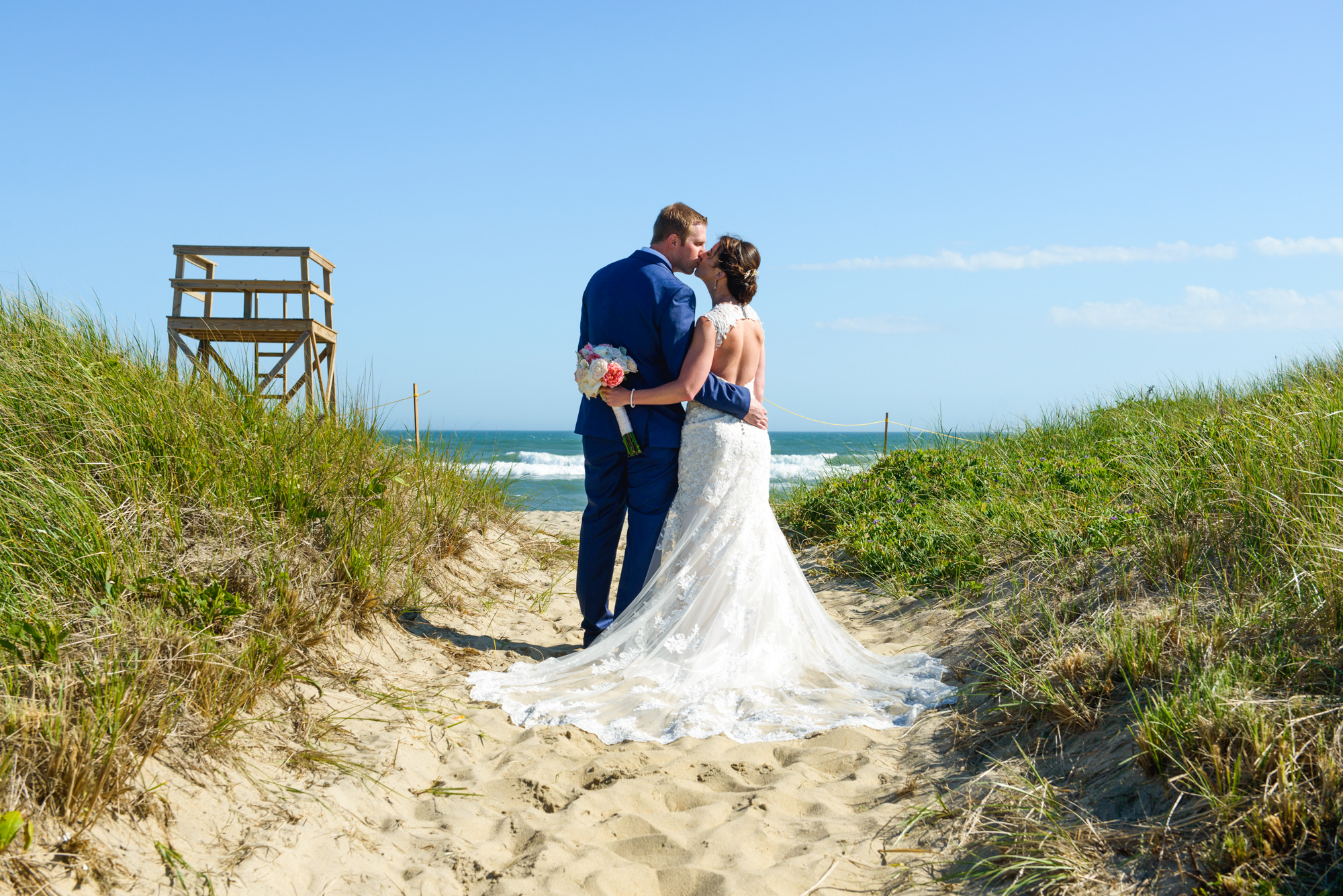 A bride and groom pose at South Beach Martha's Vineyard  photo by David Welch Photography