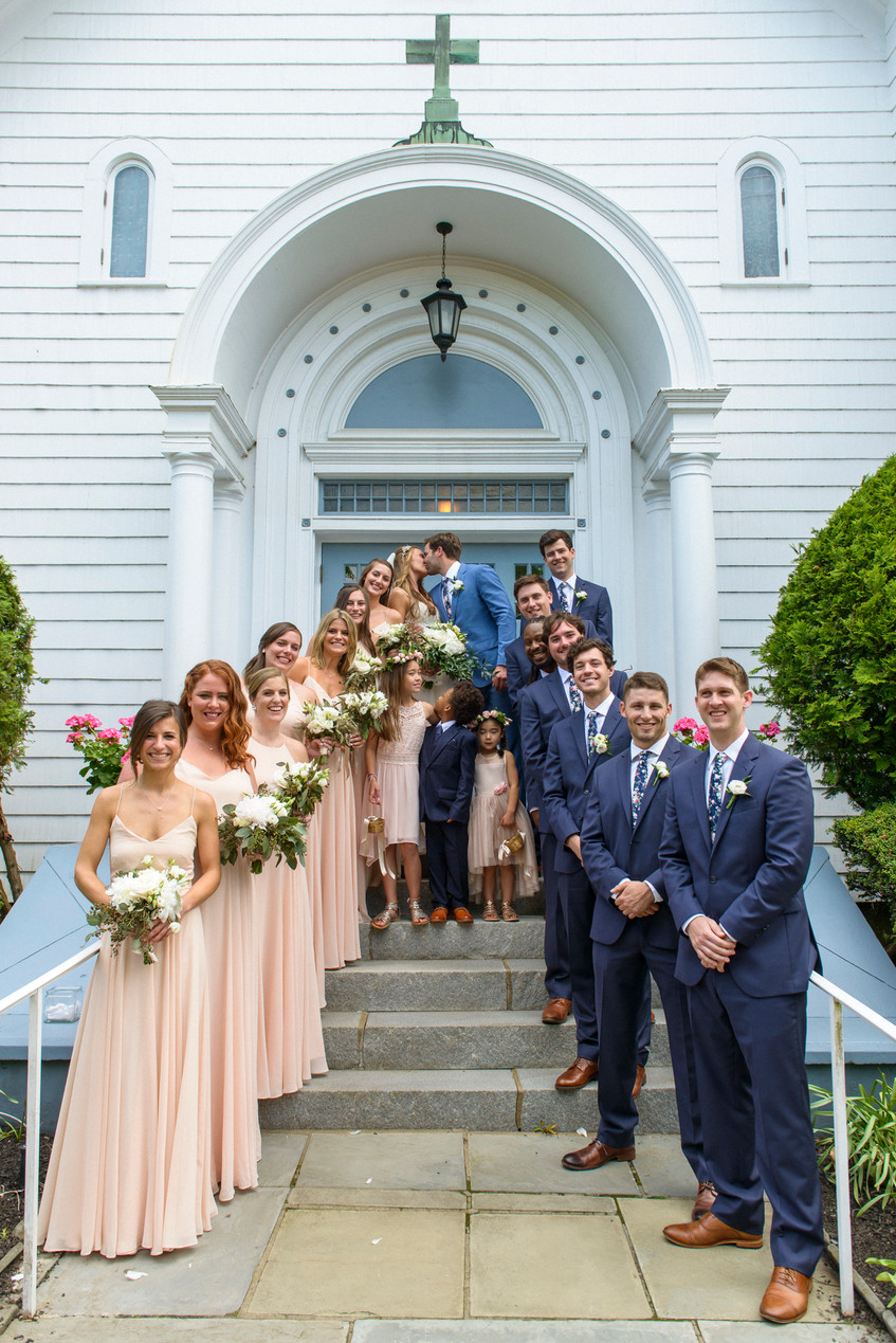 A bride and groom and their wedding party on the steps of St. Elizabeth's church in Edgartown photo by David Welch Photography