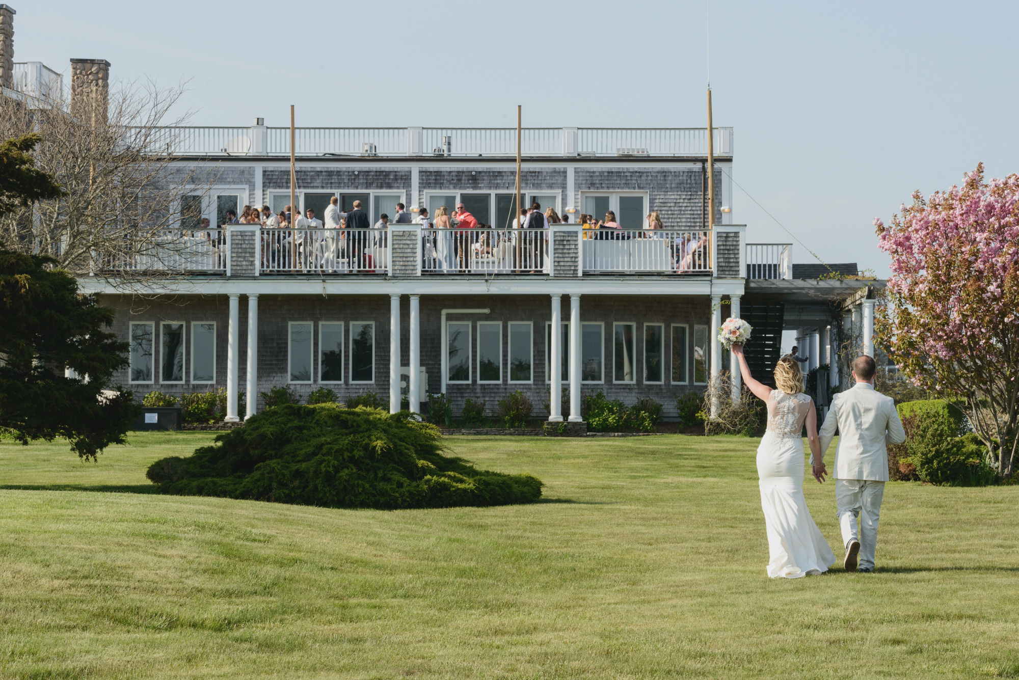 A bride and groom walk towards the Winnetu Oceanside Resort martha's vineyard wedding venues photo by David Welch Photography