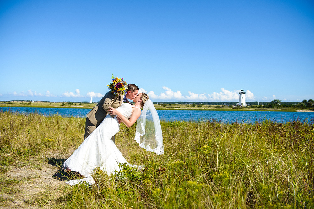 A groom dips his bride near the Edgartown Lighthouse photo by David Welch Photography