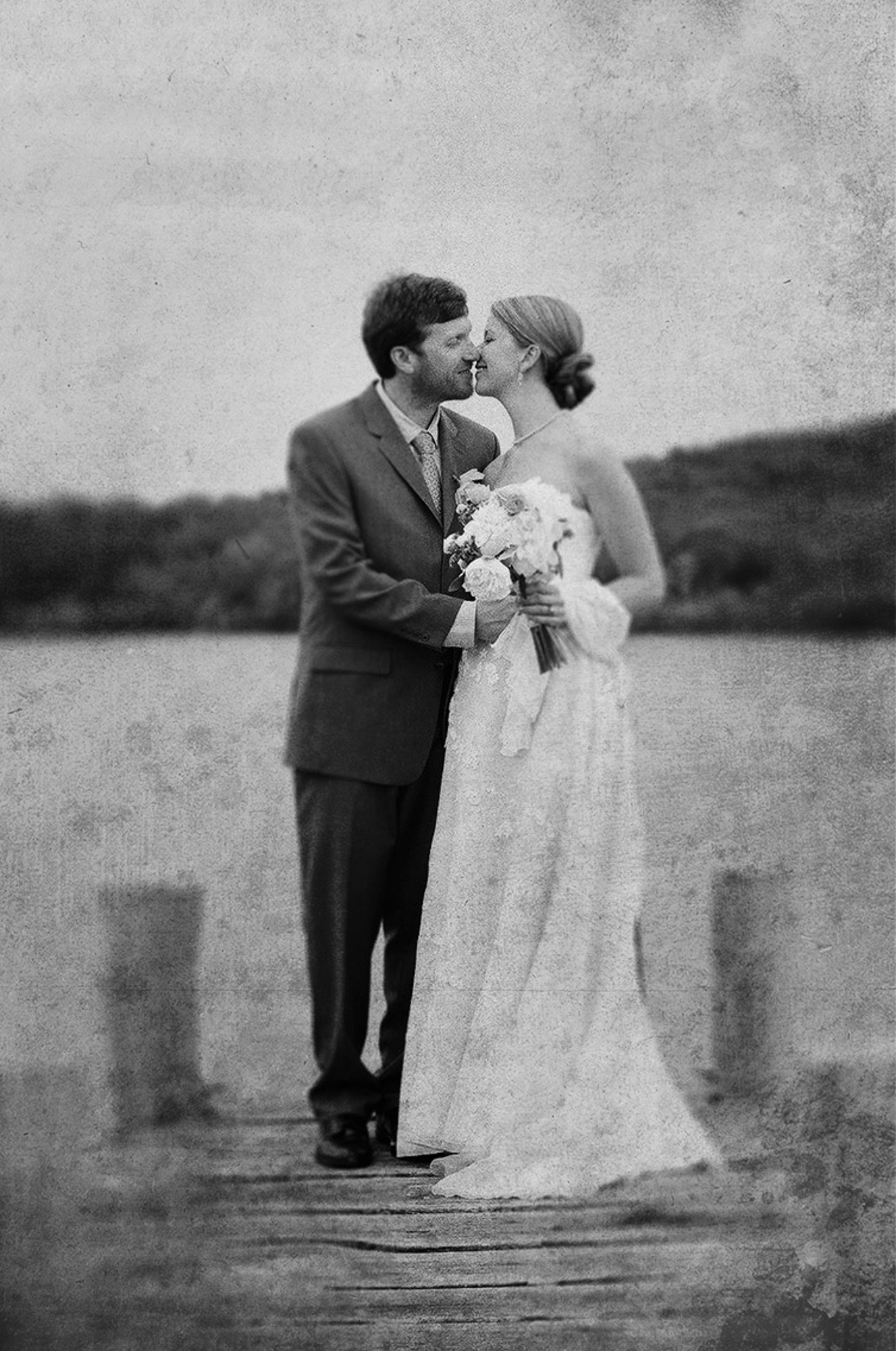 A bride and groom stand on a pier near Allen Sheep Farm in Chilmark black and white film photo by David Welch Photography