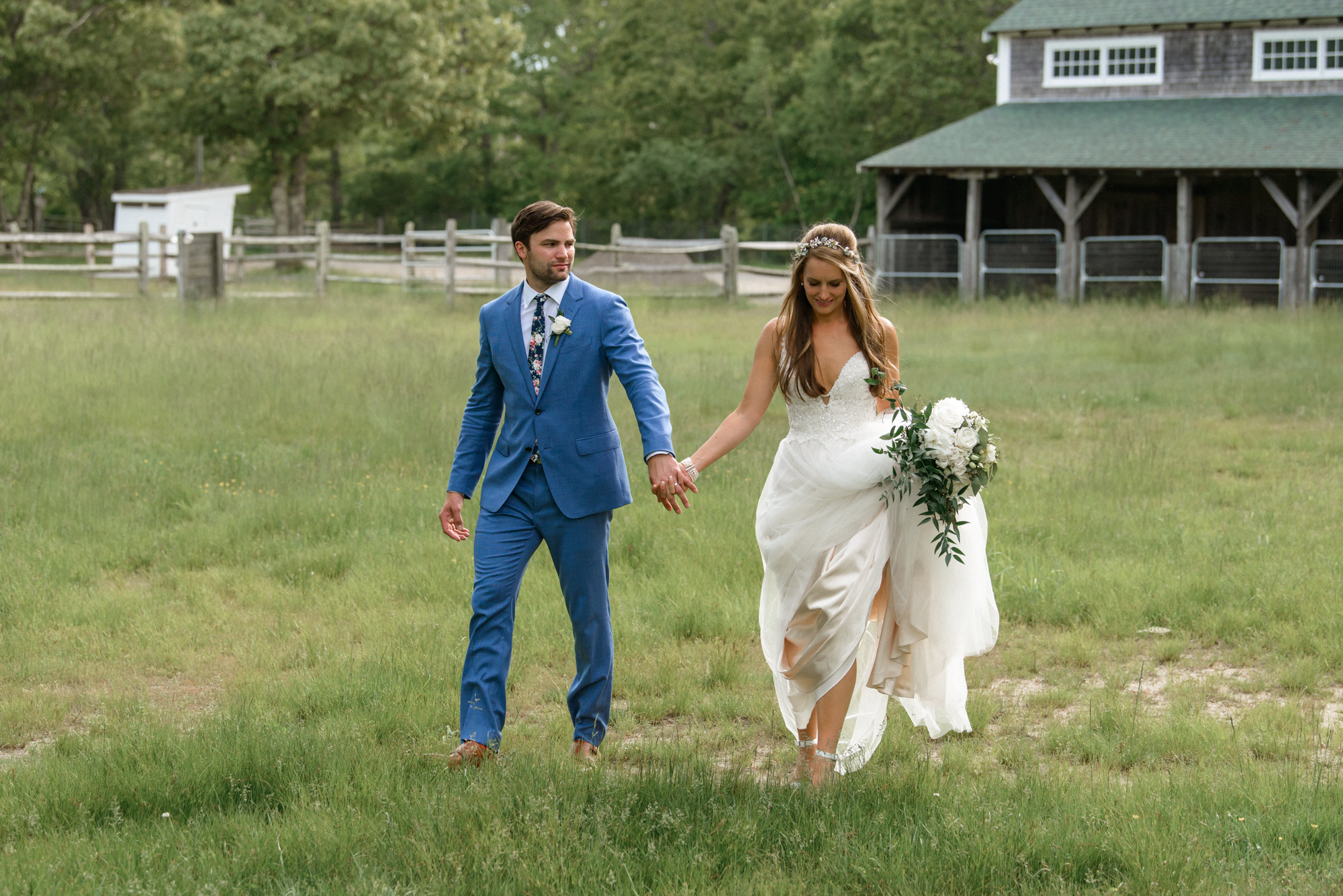 A bride and groom walk hand in hand near the Martha's Vineyard Agricultural Hall in West Tisbury photo by David Welch Photography