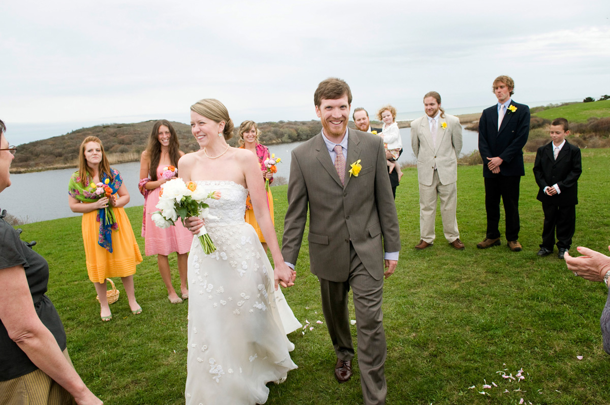 A bride and groom walking at Allen Sheep Farm in Chilmark  photo by David Welch Photography