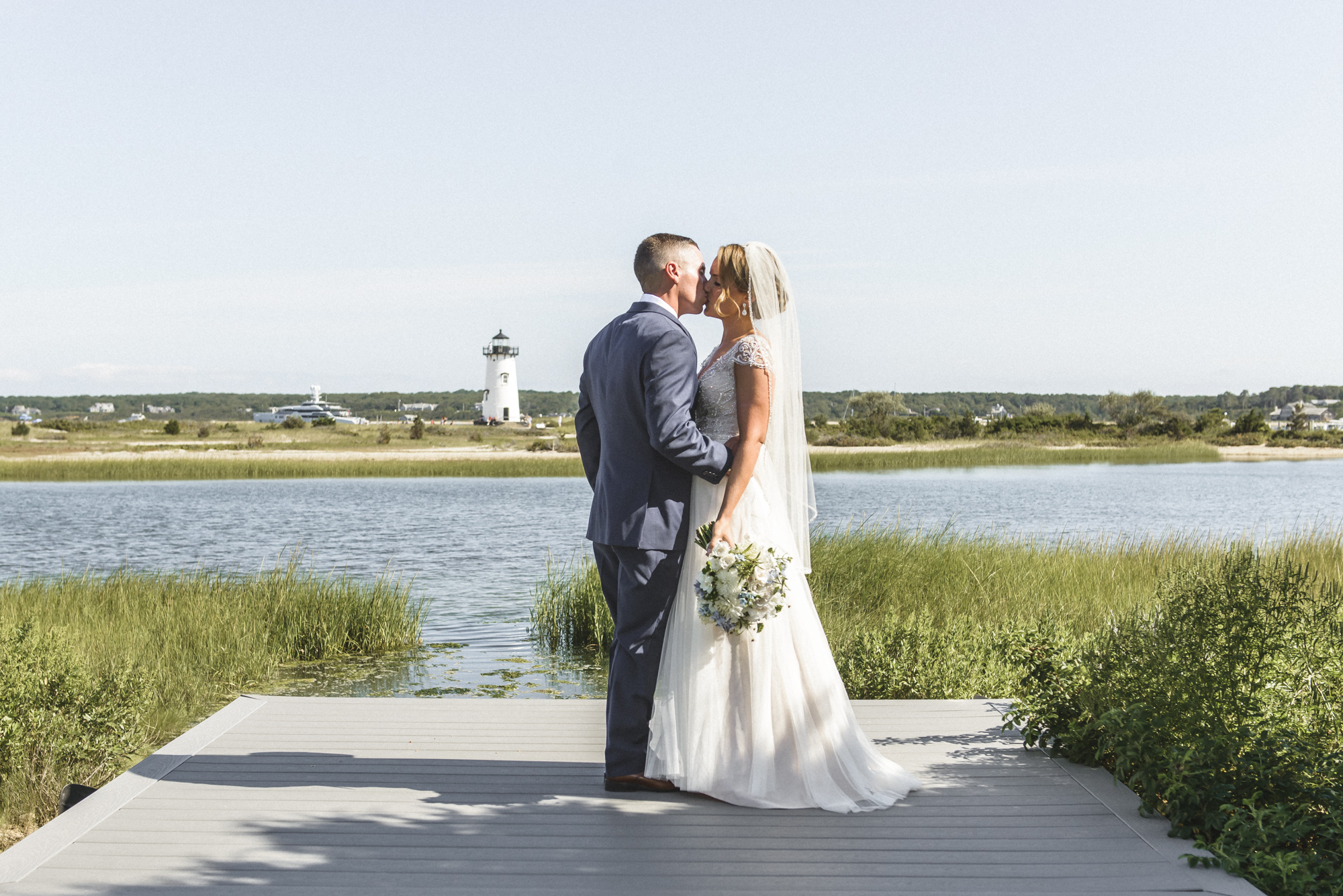 A bride and groom kiss after their first look by the Edgartown Lighthouse photo by David Welch Photography