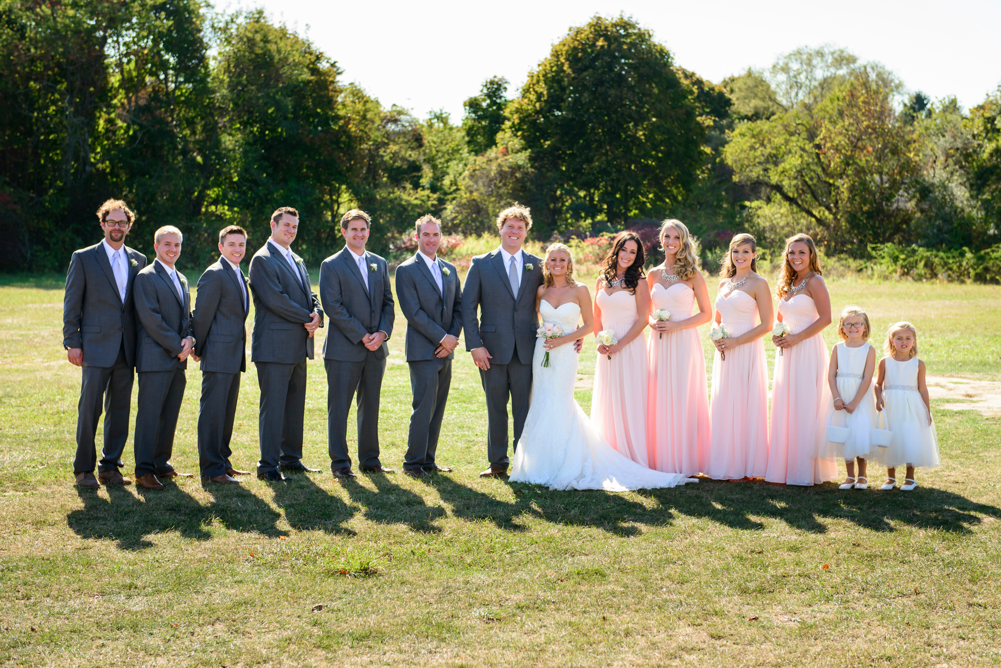 A bride and groom with groomsmen and bridesmaids on a field behind the Grange Hall in West Tisbury photo by David Welch Photography