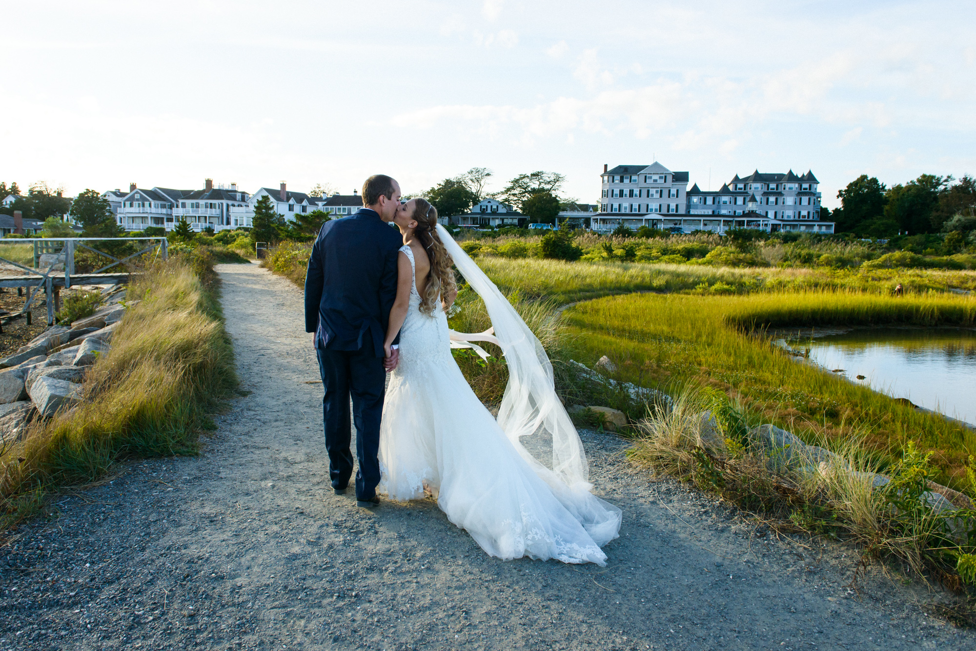 Bride and Groom walking the jetty towards the Harbor View Hotel  photo by David Welch Photography