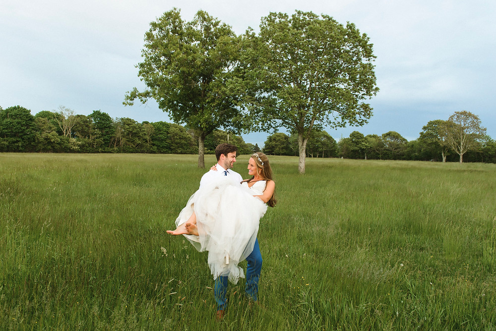A groom holding his bride on the grounds on of the Martha's Vineyard Agricultural Society's Ag Hall photo by David Welch Photography