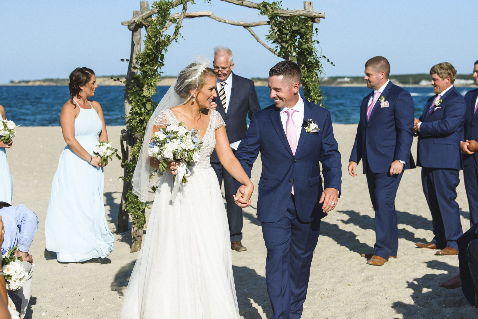 Newlyweds exit their wedding ceremony at the Edgartown Lighthouse photo by David Welch Photography