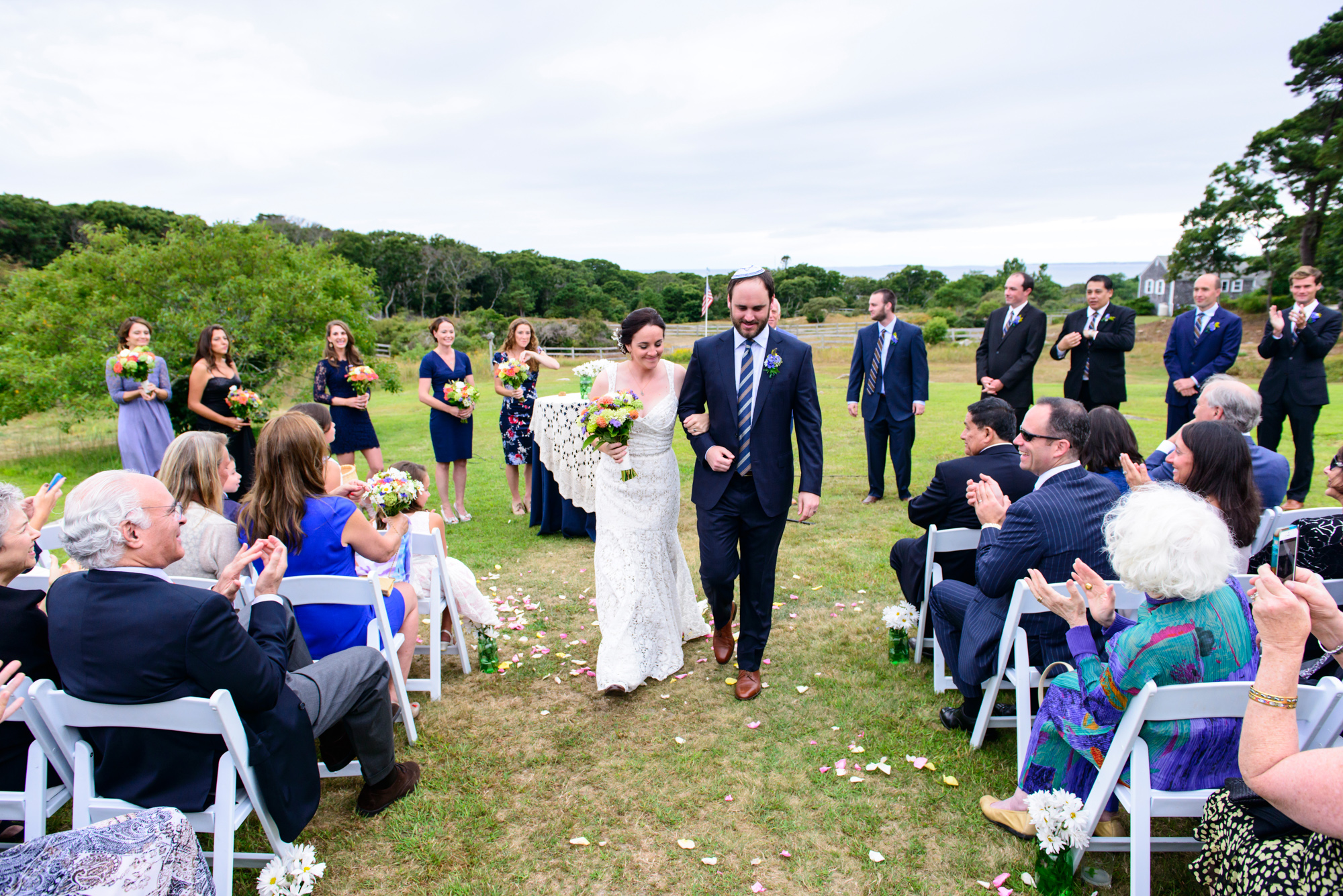 A bride and groom exit their ceremony at the field at The Beach Plum Inn & Restaurant photo by David Welch Photography