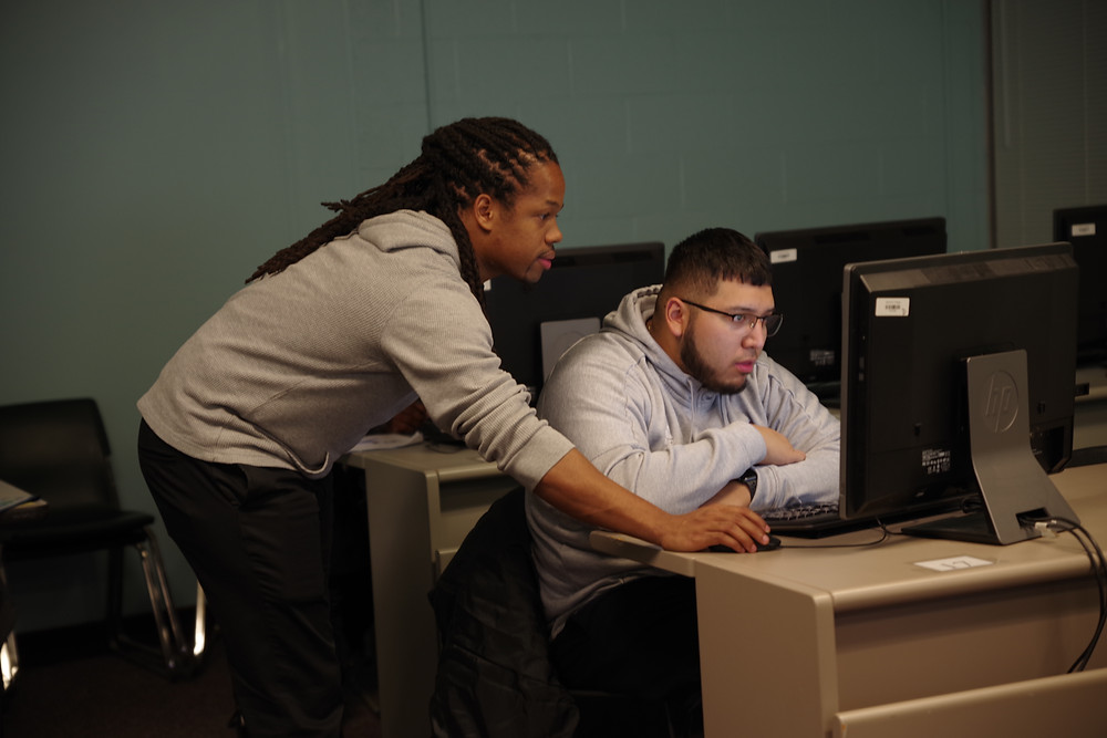 Dondreá Brown assisting a student at the computer