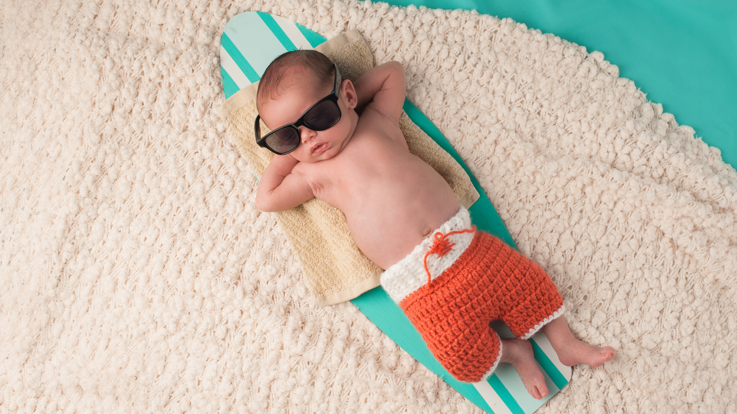 Newborn baby boy sleeping on a tiny surfboard.jpg He is wearing black sunglasses and crocheted boardshorts
