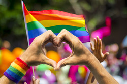 Supporting hands make heart sign and wave in front of a rainbow flag flying on the sidelines of a su