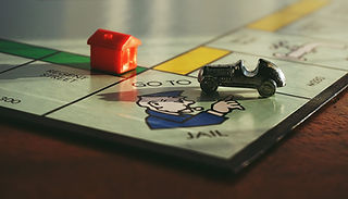 Monopoly board with car token on 'Go to jail' tile