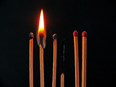 matches burnt out, one on fire. two matches on the right are unlit. the background is black