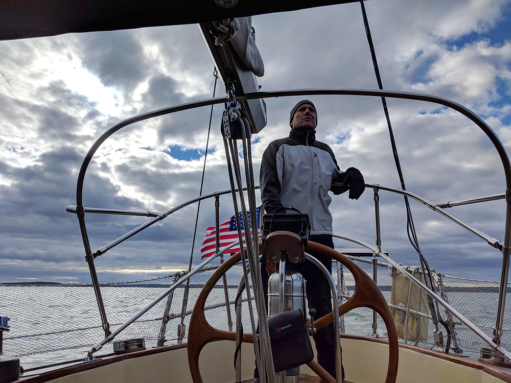 Brandon Cristiano at the helm of the  Emerald of Pleiades off the coast of Maine.