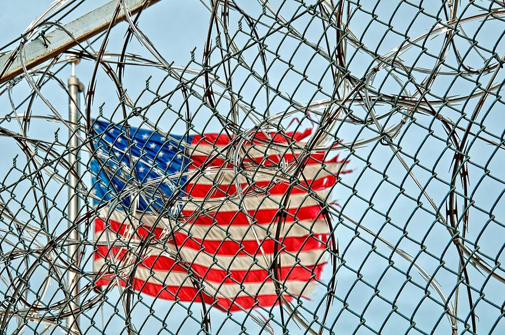 Flag behind prison fencing