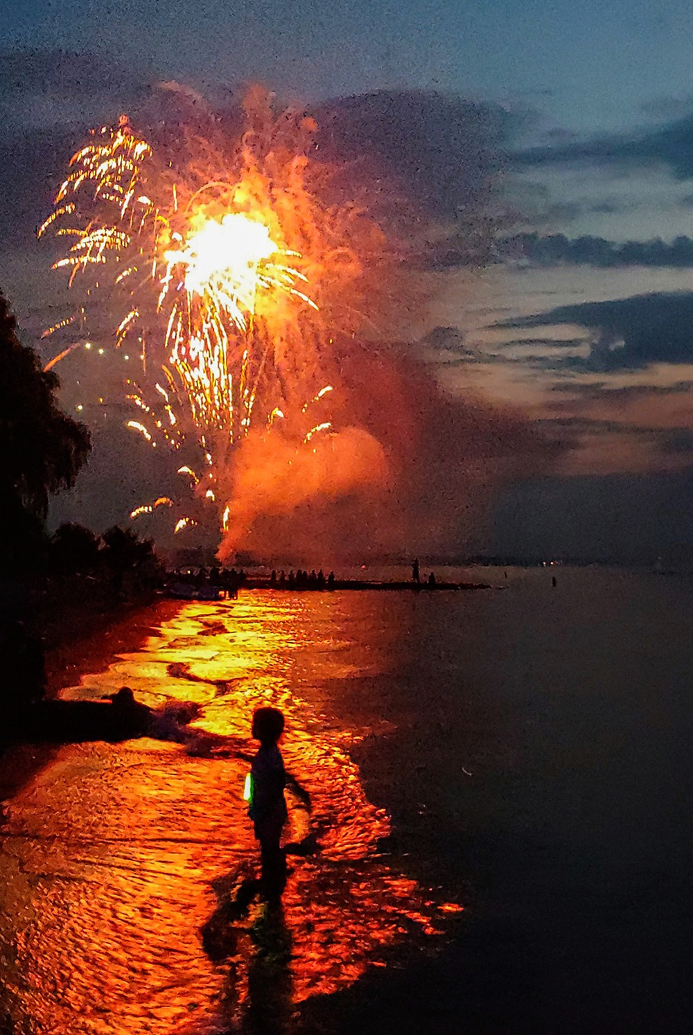 Child plays on the beach as fireworks explode overhead
