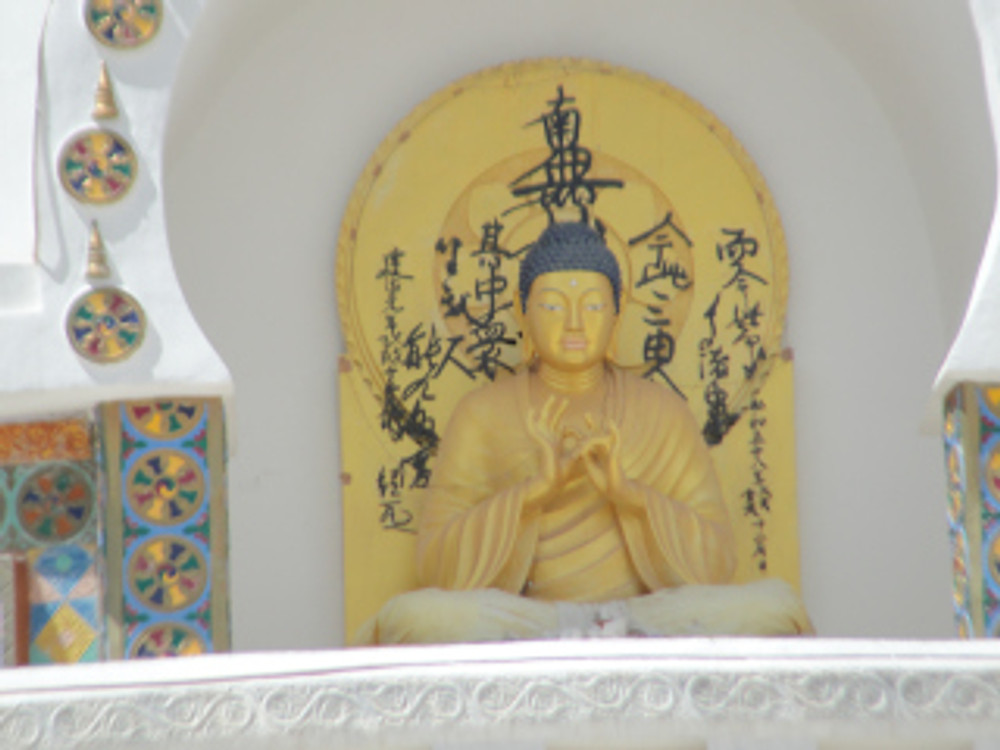 """The golden Buddha at the centre of the stupa depicts the """"Turning Wheel of Dharma""""."""