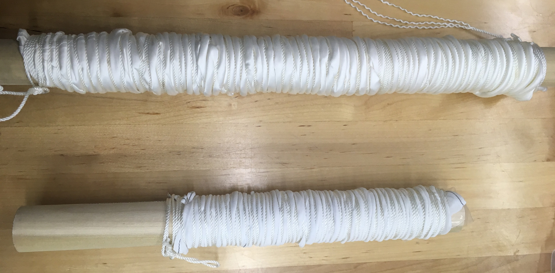 Silk is wrapped around a dowel, and thin cording wrapped on top, pushing the silk to the top of the dowel to make pleats.