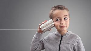 Boy on tin can phone listening to curious good news.jpg