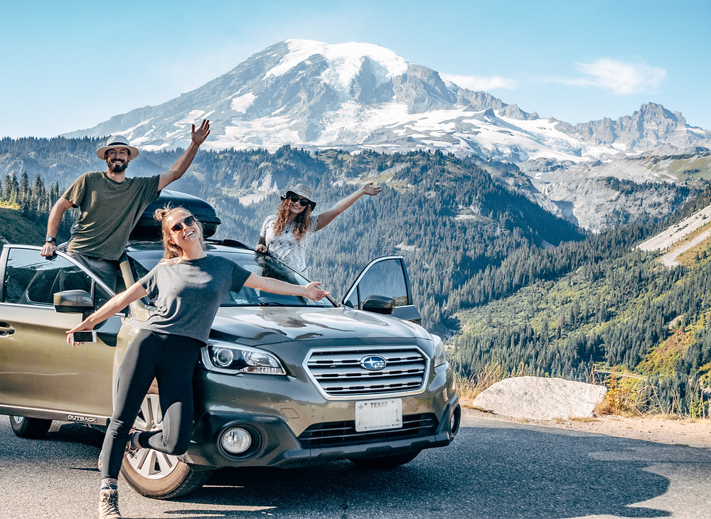 Three people with a car in front of a mountain