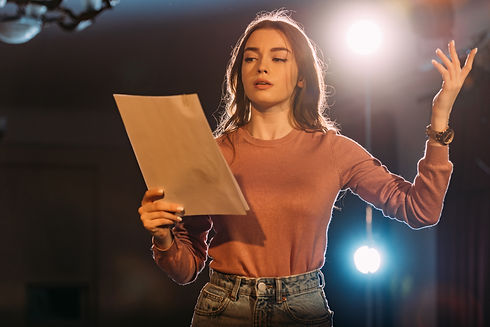 young actress reading scenario on stage