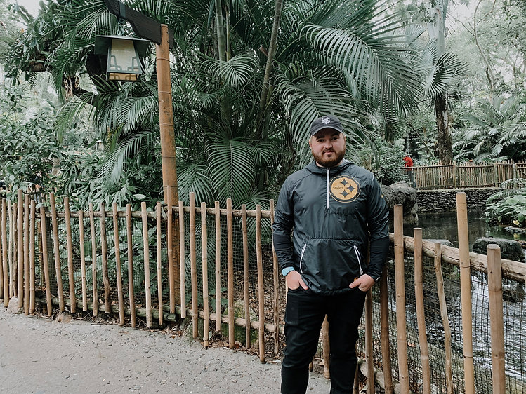 Aaron Woods wearing a Pittsburgh Steelers jacket standing in front of trees.