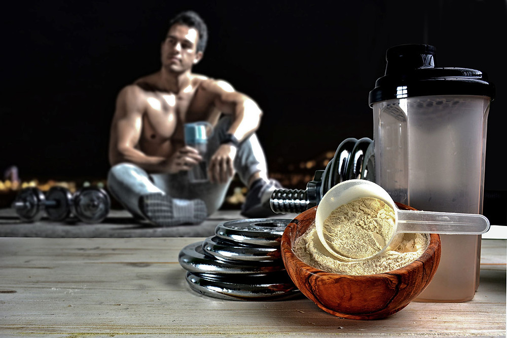 Bowl of protein powder and shaker bottle in foreground, with muscled man drinking a protein shake in the background, surrounded by weights.