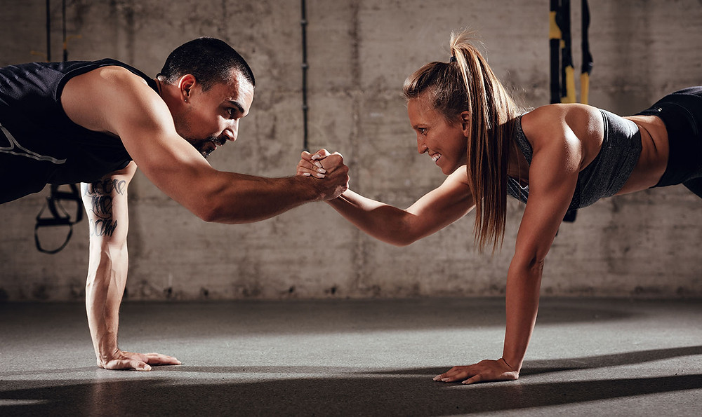 Fit man and woman in workout clothes, linking hands to steady themselves during a strength training workout in a gym.