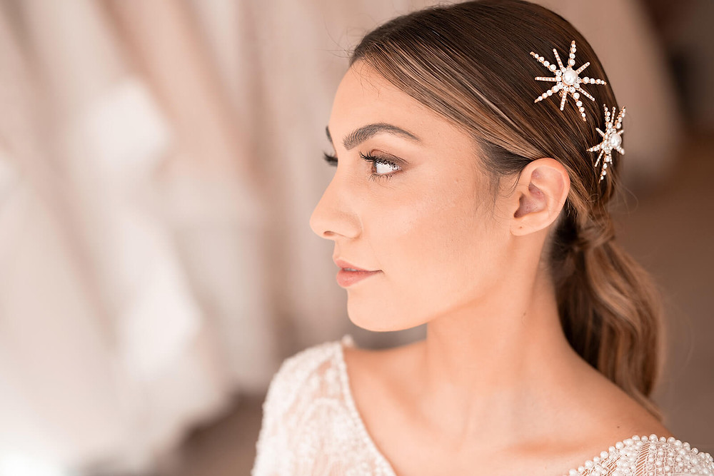 A bride with her hair and makeup done in her wedding dress appointment trying on wedding dresses and hair accessories.