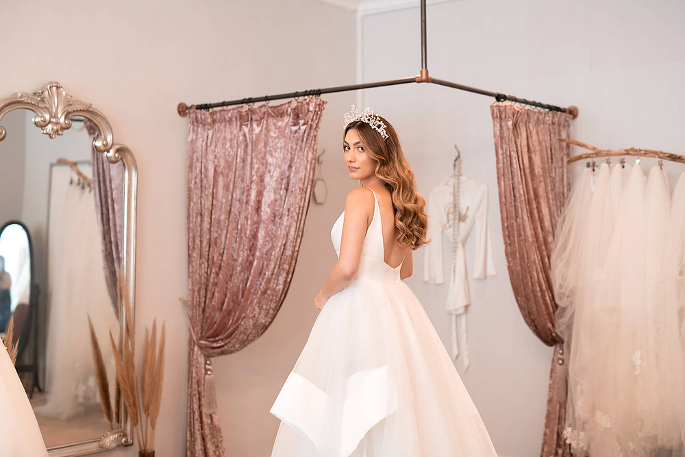 A bride trying on an ivory princess wedding dress with a cascading hem and low back.