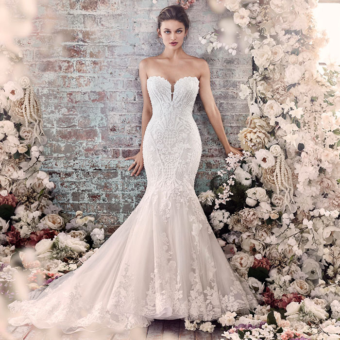 Model posing in a strapless, fishtail, lace embroidered wedding dress a part of the bridal trunk show