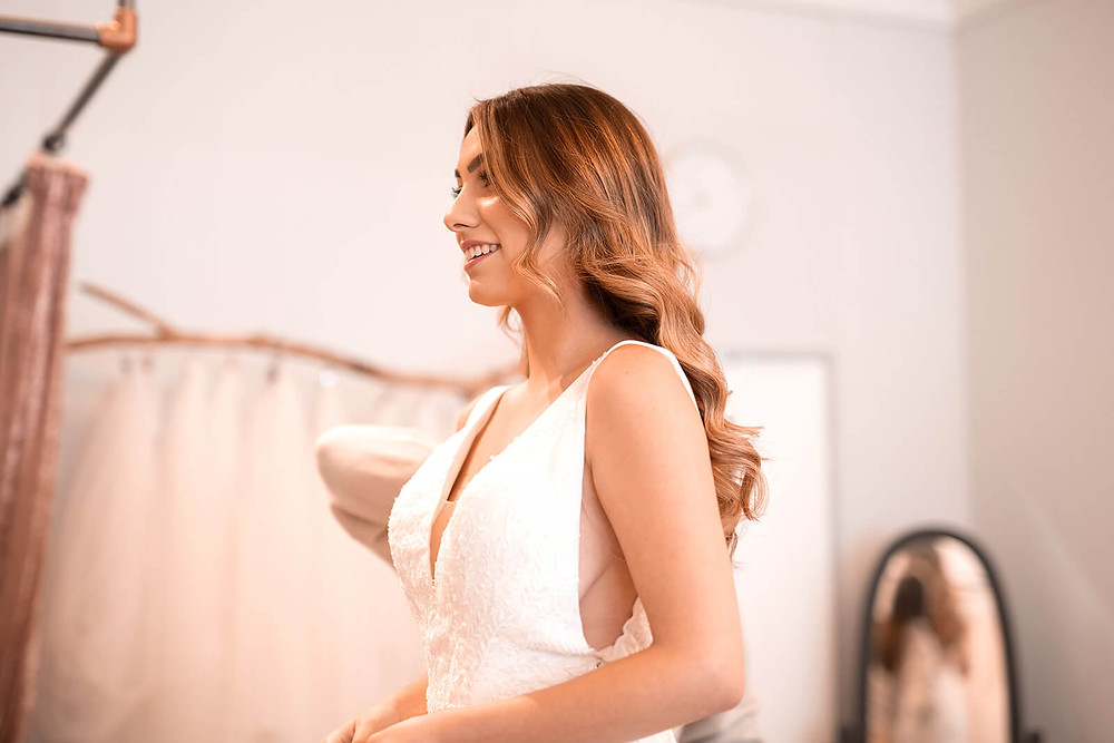 A bride looking in to the mirror in her wedding dress appointment wearing a Dando London ivory wedding dress.