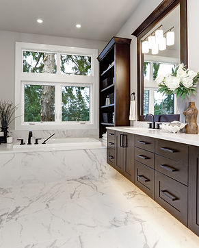 Master modern bathroom interior in luxury home with dark hardwood cabinets, white tub and