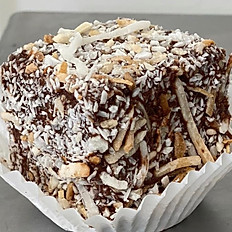 Lamington, filled with jam, rolled in chocolate, dusted in coconut