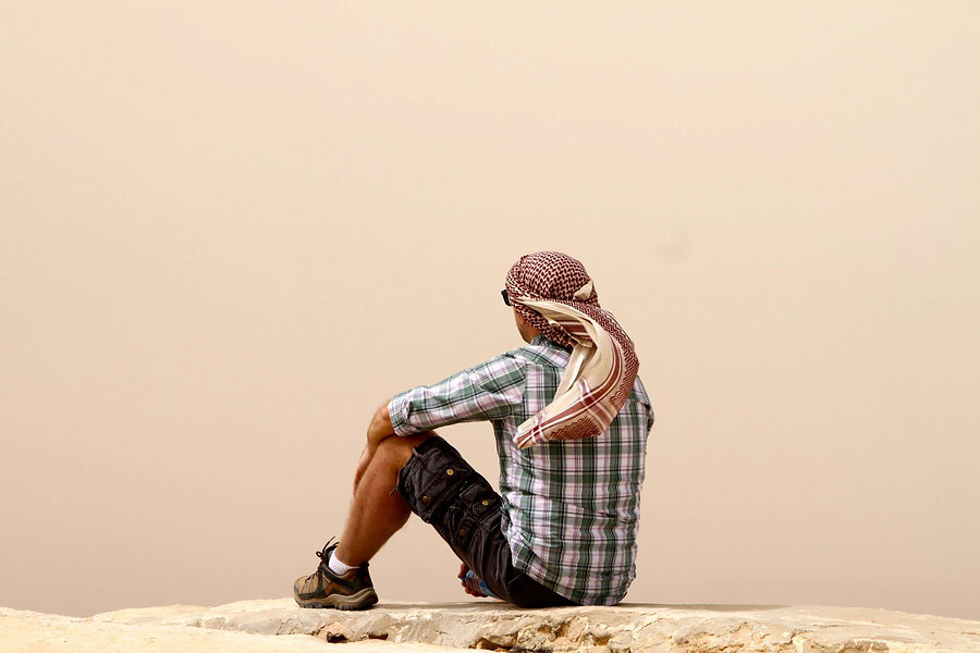 Man sitting on a stone ledge in Petra Jordan