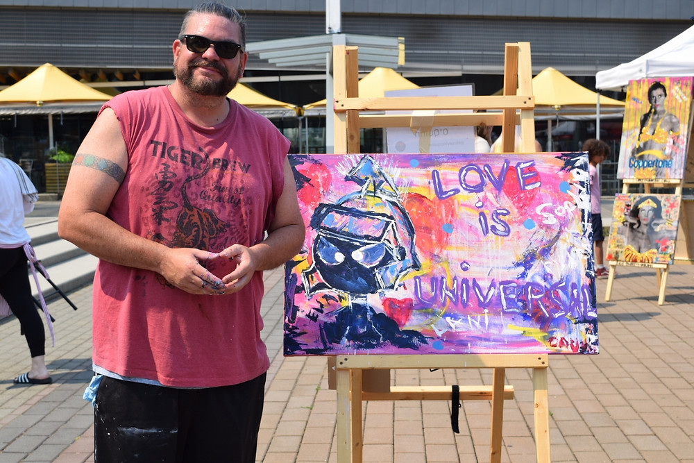 """A man stands in front of a colourful painting that reads """"Love is Universal""""."""