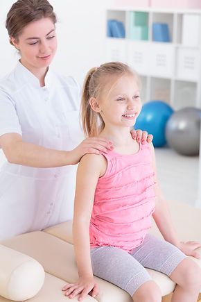 Smiling little girl on a massage table being given a back massage by a young physiotherapist