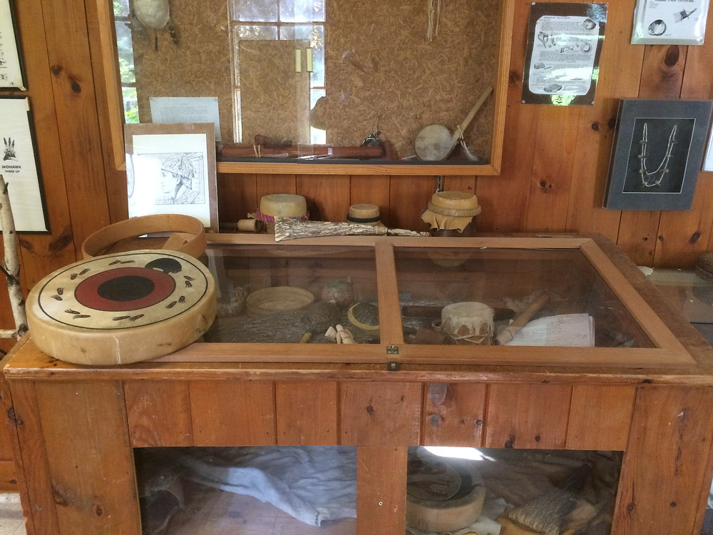 A rawhide drum (front, to the left), some Mohawk water drums (seated on the rear of the top of the display case), a bone rattle (in the rear, next to the left-most water drum) and some turtle rattles (inside the display case, center)