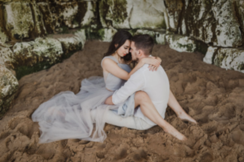 Elopement couple sitting embracing in a sea cave on a beach in Kent