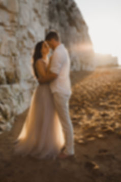 eloping couple embrace on the beach by a cliff at sunset kent