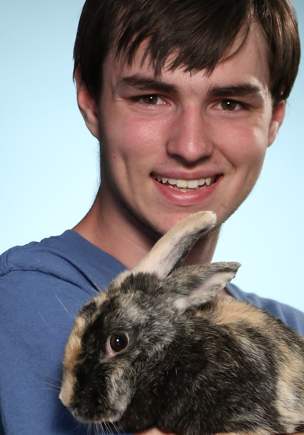 Caleb Smith holding Harley, a rare harlequin rabbit