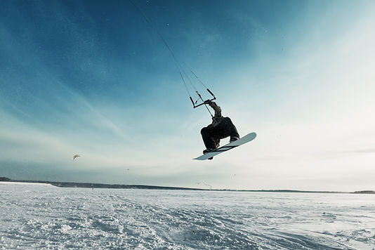kiting on a snowboard on a frozen lake.j