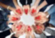Group of hands holding red ribbon stop d