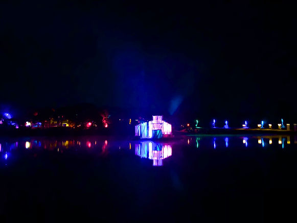 illuminated installation at night on a lake at a festival