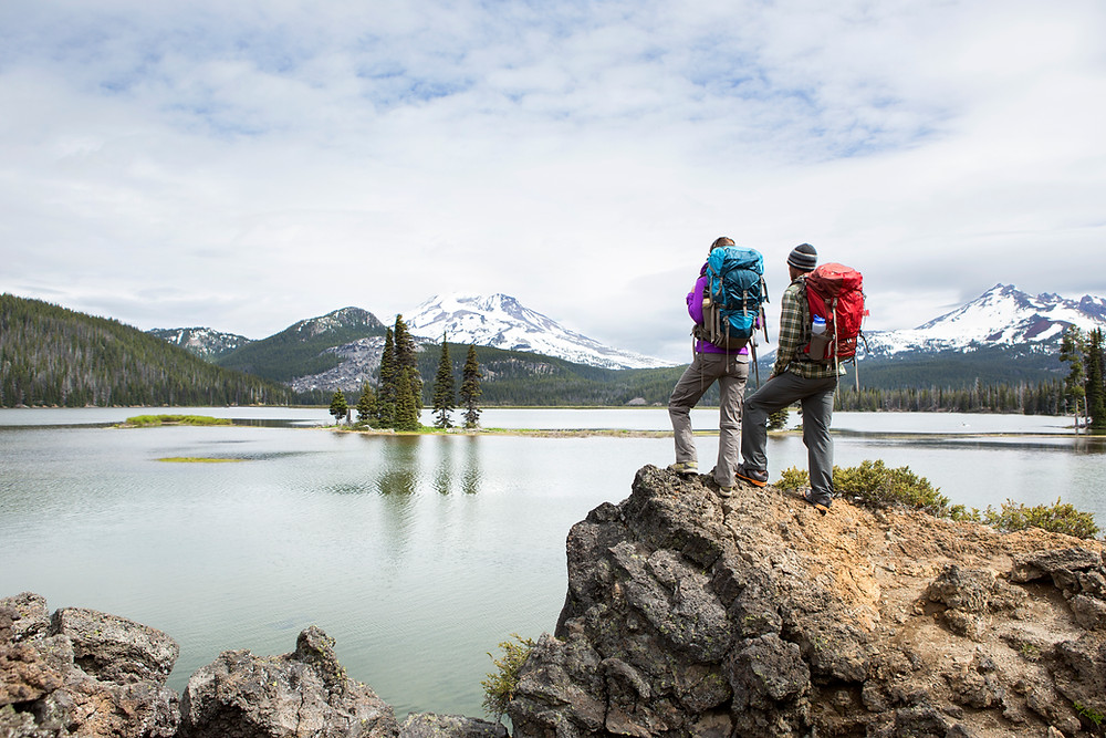 Hikers overlooking lake discuss living will vs living trust