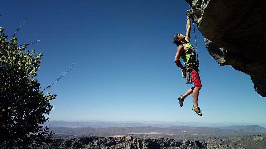Climber hanging from outcrop