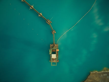 aerial view of sand dredge in blue lake.