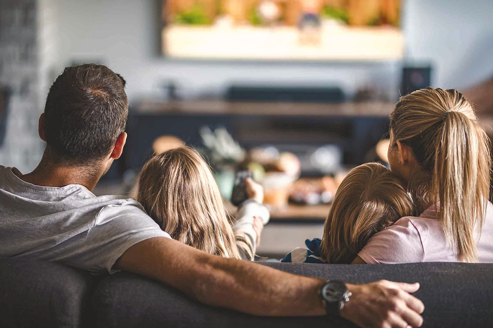 Family watching TV on upholstered couch